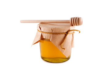 Honey in jar wooden spoon isolated white.