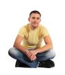 Attraktiver Mann sitzt im Schneidersitz