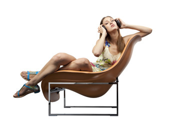 Female sitting in the fashionable chair listening to music
