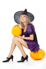 young blonde witch sitting on a pumpkin, holding a pumpkin