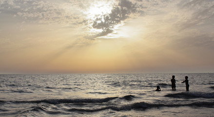 bambini che giocano in mare al tramonto