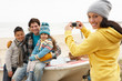 Mother Taking Family Photograph On Winter Beach