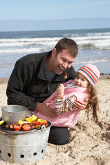 Father And Daughter Having Barbeque On Winter Beach