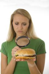 Frau untersucht kritisch einen Hamburger mit der Lupe