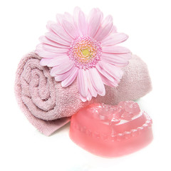 a towel, soap and flower