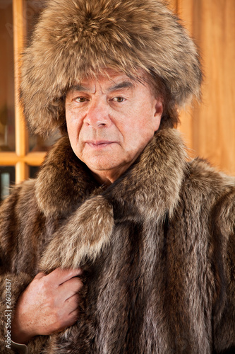 Senior man folk singer is wearing a fur hat and coat