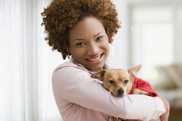 Hispanic woman holding pet dog