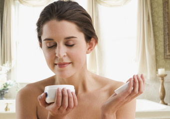 Woman smelling aroma of skin cream