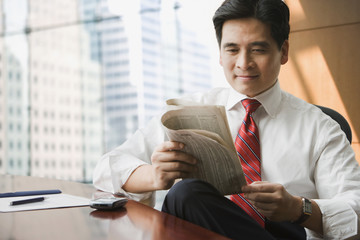Chinese businessman reading newspaper