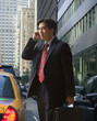Chinese businessman talking on cell phone on city street