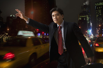 Chinese businessman hailing taxi cab
