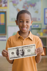 African boy holding oversized 100 dollar bill in classroom