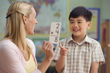 Teacher helping Asian boy learn multiplication