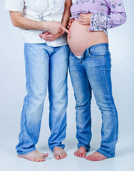 Pregnant couple in jeans. In the studio