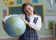 Hispanic girl holding large globe in classroom