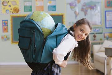 Hispanic girl carrying large globe in backpack