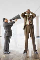 Short businessman speaking with bull horn to tall businessman