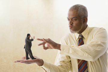 Giant businessman flicking miniature businessman