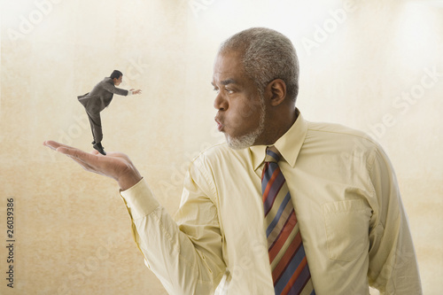 Giant businessman blowing on miniature businessman