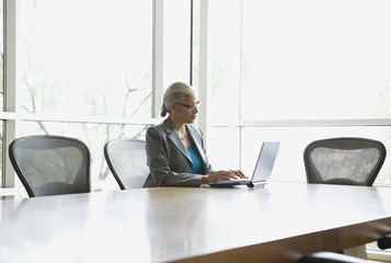 African businesswoman typing on laptop in conference room