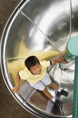 Asian boy sliding down circular slide