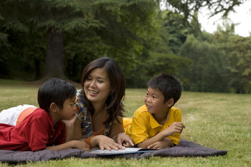 Asian mother reading book to sons in park