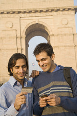 Indian friends with cell phone and credit card near the India Gate