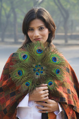 Indian woman holding peacock feather fan