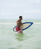 Hispanic man carrying surfboard while wading in ocean