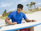 Hispanic man waxing surfboard at beach