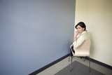 Hispanic businesswoman sitting in corner