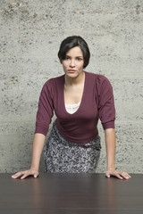 Angry Hispanic businesswoman leaning on table