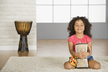 Mixed race girl holding drum