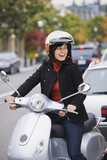 Mixed race woman in helmet driving scooter