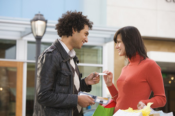Middle Eastern man giving girlfriend credit card