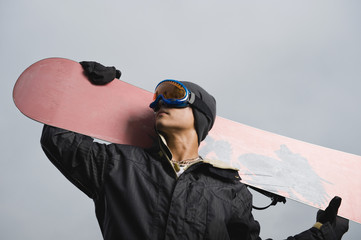 Mixed race teenager standing with snowboard