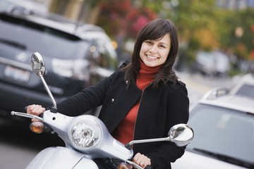 Mixed race woman driving scooter