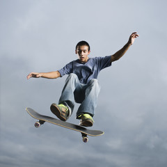 Mixed race teenager in mid-air on skateboard