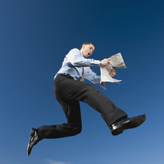 African businessman reading newspaper in mid-air