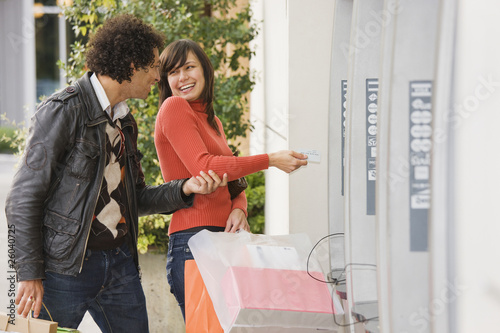 Couple with shopping bags at ATM