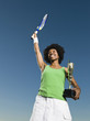African woman holding tennis racquet and trophy