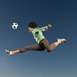 African woman playing soccer in mid-air