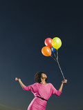 African woman holding bunch of balloons