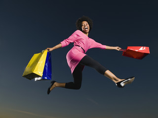 African woman holding shopping bags in mid-air
