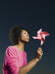 African woman blowing pinwheel