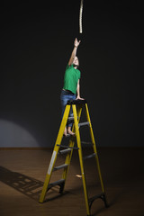 Hispanic girl on ladder reaching for rope