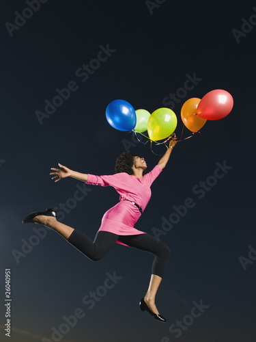African woman holding bunch of balloons in mid-air