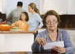 Hispanic woman reviewing bills in kitchen