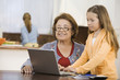 Hispanic girl showing grandmother how to use computer