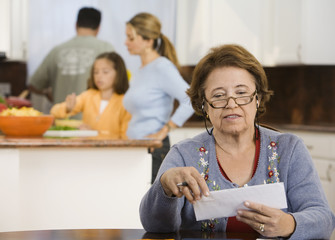 Hispanic woman reviewing bills in kitchen